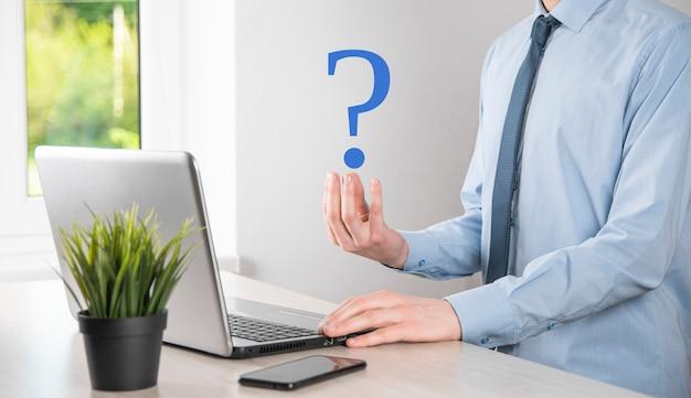 Homme d'affaires main tenir les points d'interrogation de l'interface web. posez des questions en ligne, concept de faq, quoi où quand comment et pourquoi, recherchez des informations sur internet
