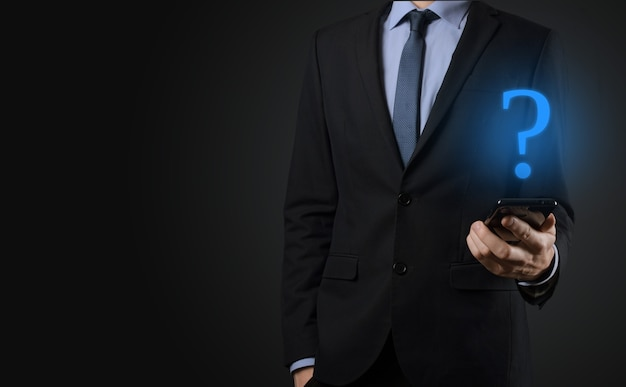 Homme d'affaires main tenir les points d'interrogation de l'interface web. posez des questions en ligne, concept faq, quoi où quand comment et pourquoi, recherchez des informations sur internet.