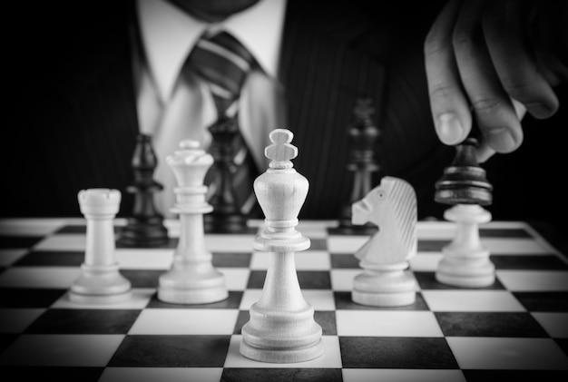 Homme affaires, main, tenue, a, pièce échecs, sur, a, échiquier