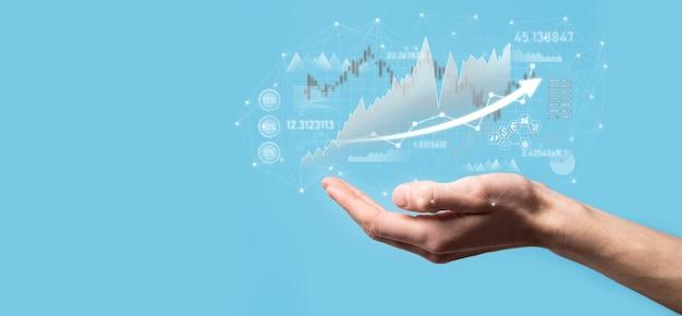 Un homme d'affaires en main tient un graphique de financement d'entreprise bancaire et investit dans un point d'investissement boursier, une croissance économique et un concept d'investisseur.