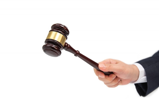 Un homme d'affaires main tient un marteau de juge en bois isolé on white