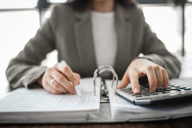 Homme d'affaires mains calculant la facture avec la calculatrice