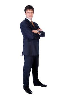 Homme d'affaires avec les mains croisées debout contre le mur isolé