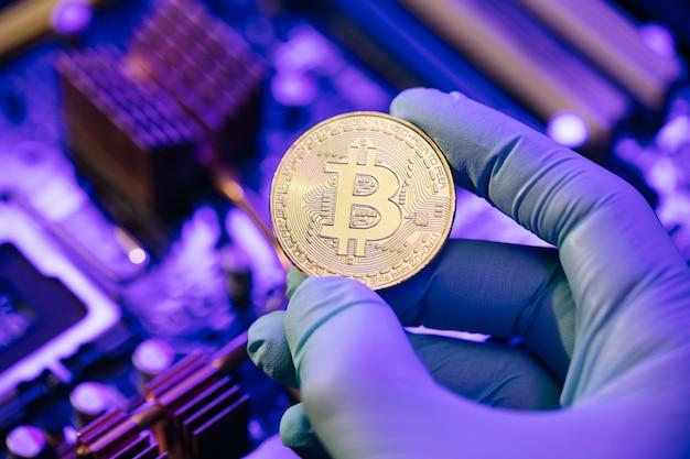 Homme d'affaires les mains dans les gants tiennent bitcoin or sur la carte mère
