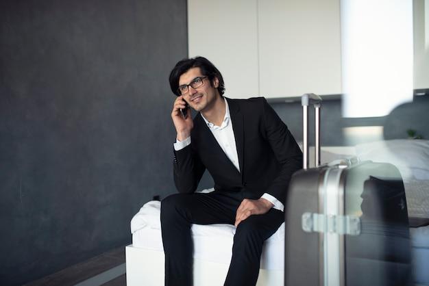 Homme d'affaires à la maison parle au téléphone prêt à voyager