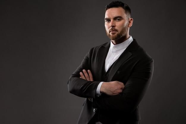 Un homme d'affaires mal rasé brutal vêtu d'un costume noir et d'une chemise blanche