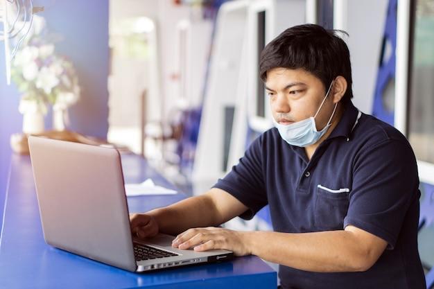 Homme d'affaires malade utiliser un ordinateur portable avec la température et les maux de tête au bureau