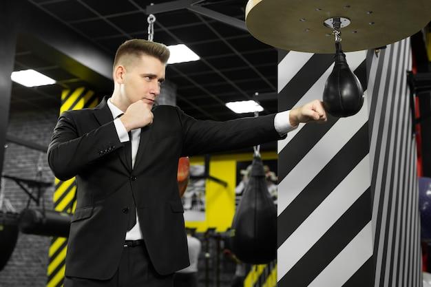 Un homme d'affaires maléfique frappe un sac de boxe dans la salle de gym. le concept de gestion de la colère.