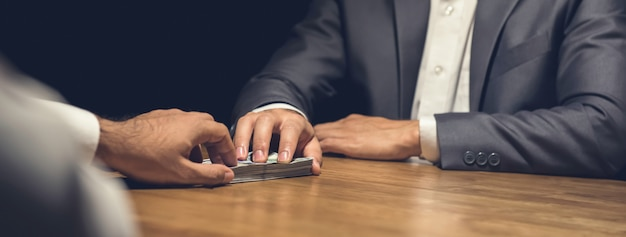 Homme d'affaires malhonnête donnant secrètement de l'argent à sa partenaire dans le noir