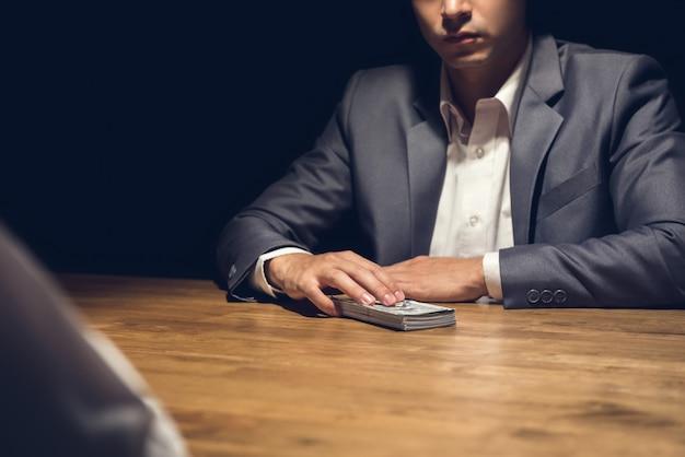 Homme d'affaires malhonnête sur le point de donner de l'argent à son partenaire dans le noir