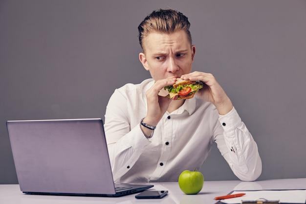 Homme d'affaires mange un hamburger au bureau tout en regardant la vidéo sur son ordinateur portable