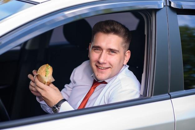 Homme d'affaires mangeant un hamburger dans la voiture