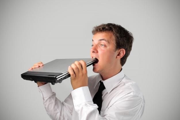 Homme d'affaires mangeant son ordinateur portable