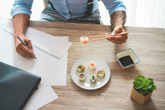 Homme d'affaires manger des sushis à l'heure du déjeuner tout en travaillant au nouveau projet