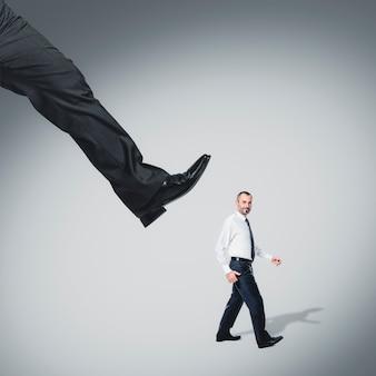 Homme d'affaires marchant calmement et un grand pied pend au-dessus de lui.