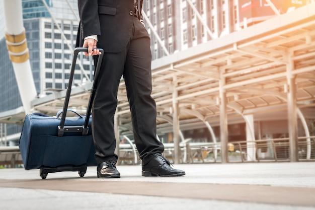 Homme d'affaires marchant sur le chemin de l'aéroport avec des bagages