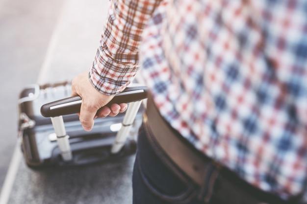 Homme d'affaires marchant à l'extérieur du bâtiment des transports en commun avec bagages en heure de pointe.
