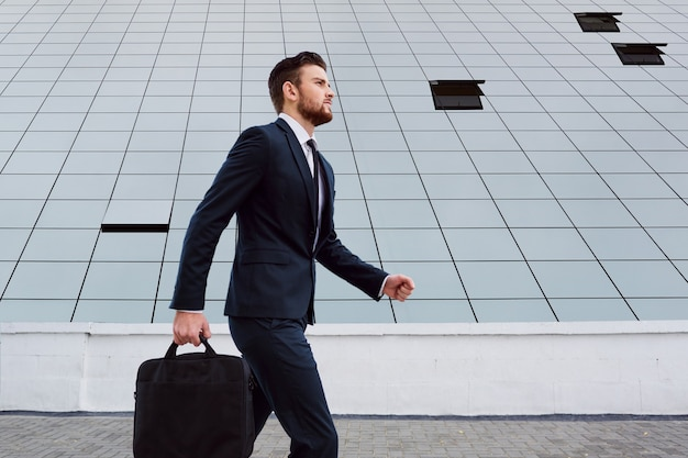 Homme d'affaires marche avec un sac sur un fond d'affaires bu