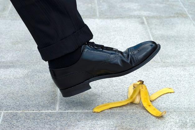 Homme d'affaires marcher sur la peau de banane