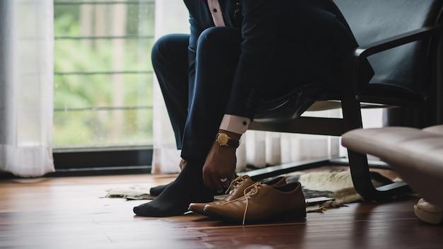Homme d'affaires ou le marié a attaché un lacet sur ses chaussures.
