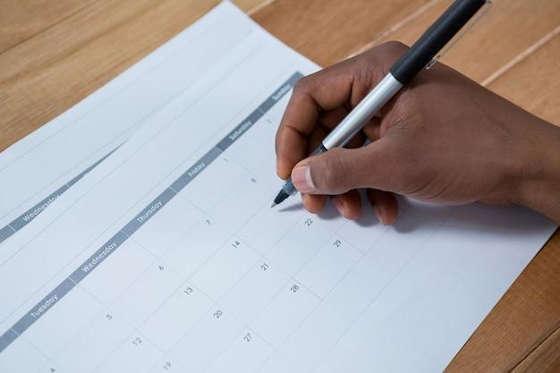 Homme d'affaires marquant avec un stylo sur le calendrier