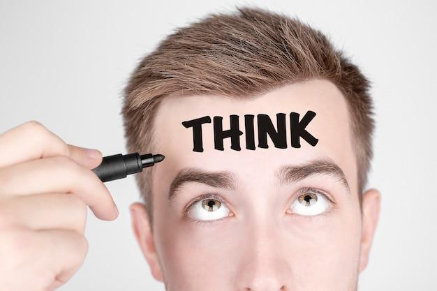 Homme d'affaires avec un marqueur noir écrit le mot pensez sur son front