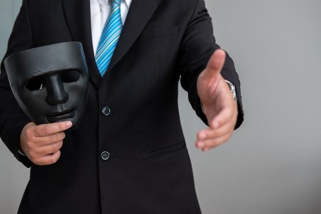Homme d'affaires avec un masque noir couvrant l'insincérité de faire des affaires ensemble.