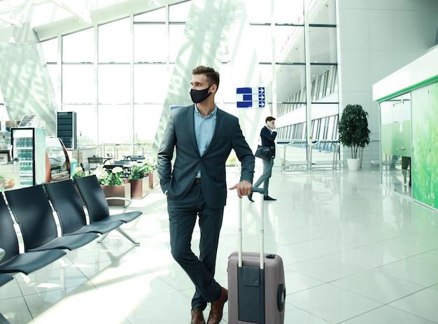 Homme d'affaires en masque de protection avec valise dans le hall de l'aéroport. aéroport dans l'épidémie de coronavirus.
