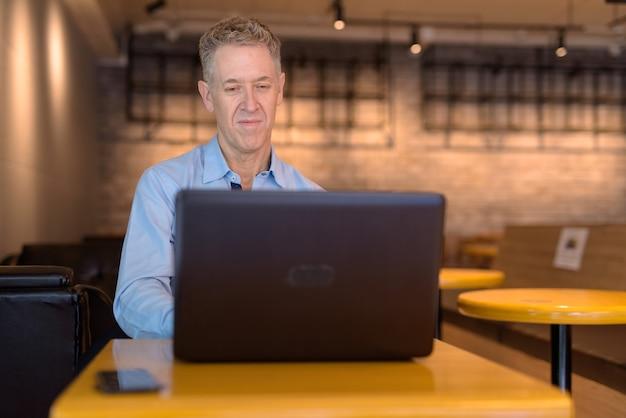 Homme d'affaires mature à l'aide d'un ordinateur portable alors qu'il était assis au café