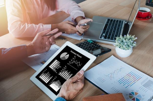 Homme d'affaires mature à l'aide d'une tablette numérique pour discuter de l'information avec un collègue plus jeune.