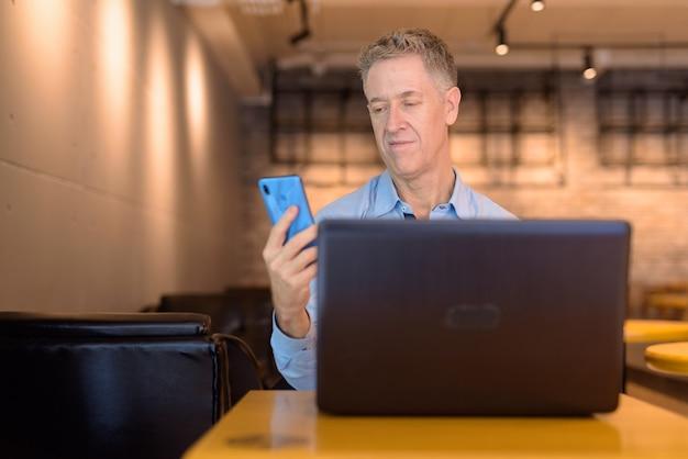 Homme d'affaires mature à l'aide de téléphone alors qu'il était assis au café