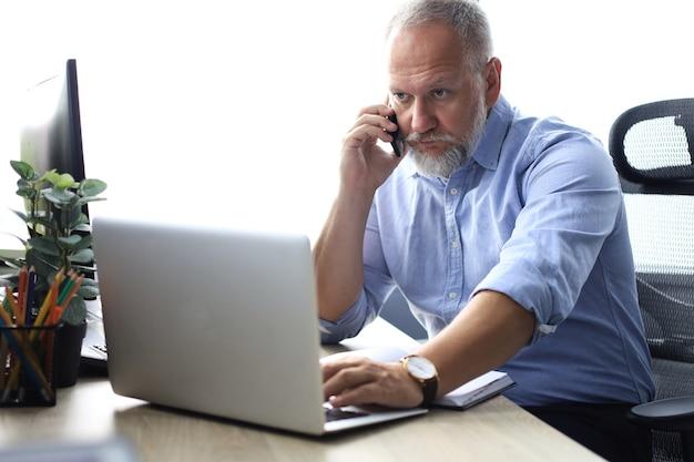 Homme d'affaires mature confiant ayant un appel téléphonique sur son smartphone dans un bureau moderne.