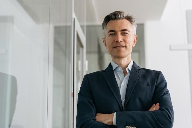Homme d'affaires mature confiant avec les bras croisés regardant la caméra, souriant debout au bureau. concept d'entreprise réussie