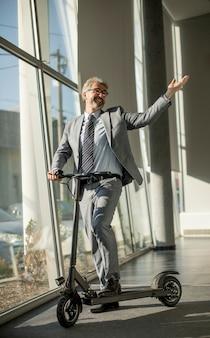 Homme d'affaires mature debout près de la fenêtre du bureau avec scooter électrique