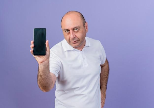 Homme d'affaires mature décontracté montrant un téléphone mobile et regardant la caméra et en gardant la main sur la taille isolé sur fond violet avec espace copie
