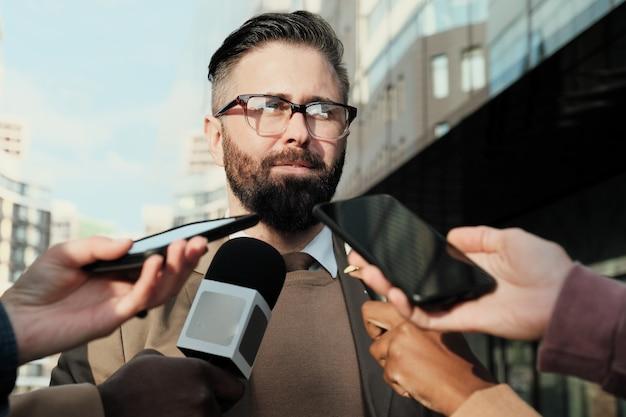 Homme d'affaires mature à lunettes interviewé avec un journaliste à l'extérieur