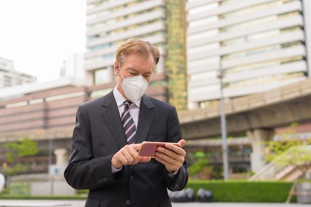 Homme d'affaires mature avec masque à l'aide de téléphone dans la ville à l'extérieur