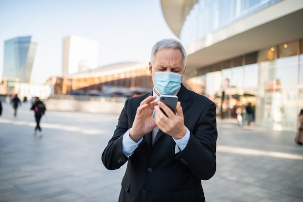 Homme d'affaires mature masqué utilisant son smartphone concept extérieur, covid et coronavirus
