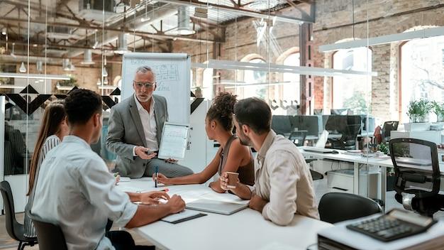 Homme d'affaires mature montrant quelque chose sur une tablette numérique à de jeunes collègues assis