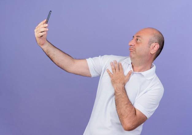 Homme d'affaires mature occasionnel confus gardant la main sur la poitrine et prenant selfie isolé sur fond violet