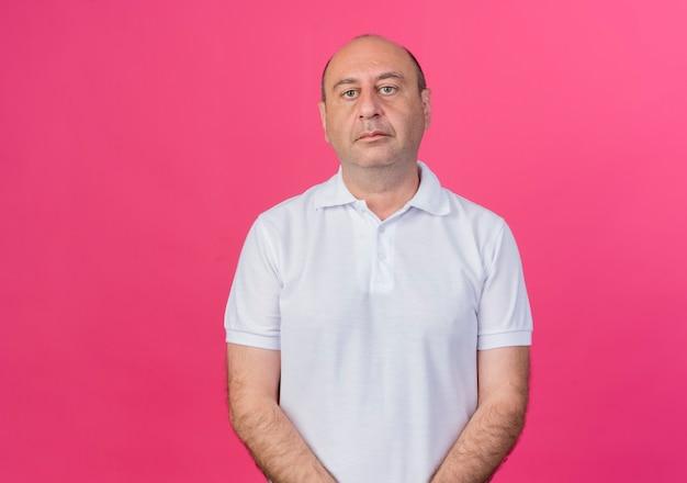 Homme d'affaires mature occasionnel debout et regardant la caméra isolée sur fond rose avec espace de copie