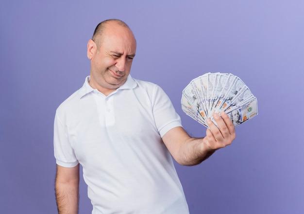 Homme d'affaires mature occasionnel douteux tenant et regardant l'argent isolé sur violet