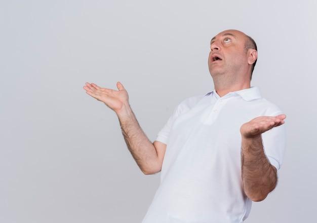 Homme d'affaires mature occasionnel impressionné en levant et en montrant les mains vides isolé sur fond blanc avec copie espace