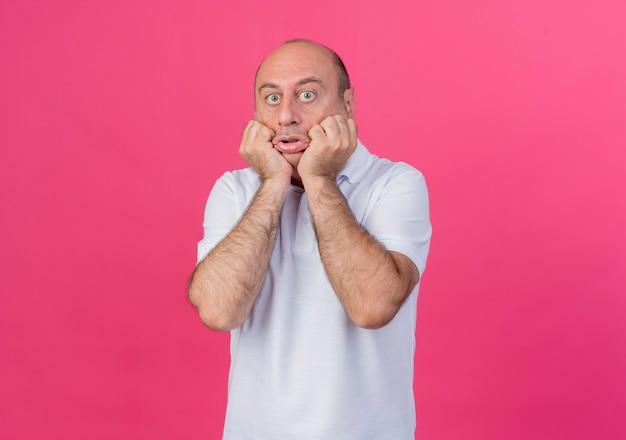 Homme d'affaires mature occasionnel impressionné mettant les mains sur le menton en regardant la caméra isolée sur fond rose avec copie espace