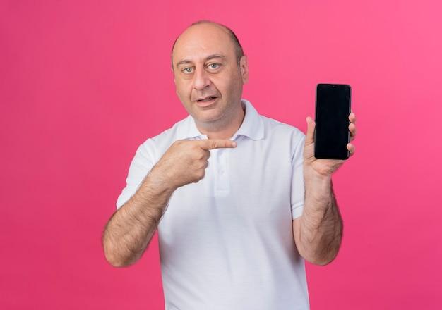Homme d'affaires mature occasionnel impressionné montrant un téléphone mobile et pointant vers lui isolé sur fond rose