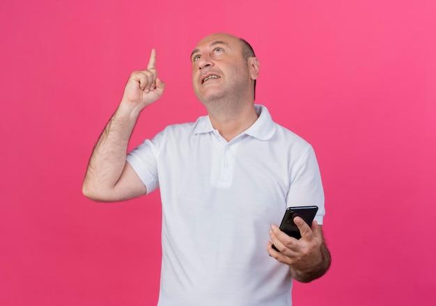 Homme d'affaires mature occasionnel impressionné à la recherche et pointant vers le haut et tenant un téléphone mobile isolé sur fond rose avec espace de copie
