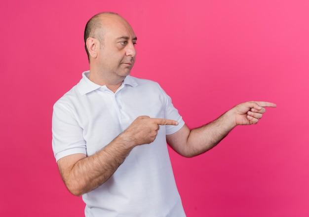 Homme d'affaires mature occasionnel à la recherche et pointant sur le côté isolé sur fond rose