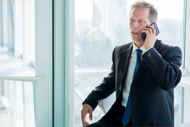 Homme d'affaires mature parlant sur smartphone