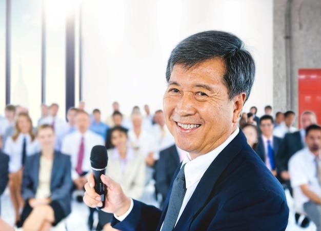 Homme d'affaires mature présentant lors d'une conférence