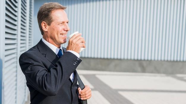 Homme d'affaires mature souriant, buvant du café à l'extérieur